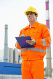 Male architect holding clipboard while standing at site Stock Image