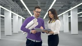 Male architect is holding drawings and talking to his female colleague stock video footage