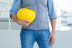 Male architect holding yellow hard hat Stock Images