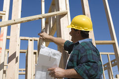 Male Architect Inspecting At Construction Site. Happy mature architect with blueprint inspecting at construction site Stock Photos