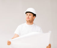 Male architect looking at blueprint. Picture of male architect in helmet looking at blueprint Stock Photography