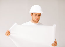 Male architect looking at blueprint. Picture of male architect in helmet looking at blueprint Royalty Free Stock Images