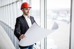 Male architect looking at blueprints in hamlet near panoramic windows Royalty Free Stock Photos