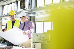 Male architect and manual worker examining blueprint in metal industry stock photography