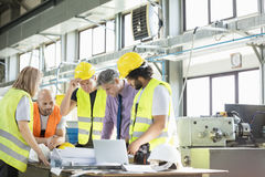 Male architect and manual workers discussing over blueprints in industry.  stock photography