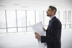 Male Architect In Modern Empty Office Looking At Plans Royalty Free Stock Photo