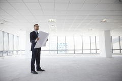 Male Architect In Modern Empty Office Looking At Plans Royalty Free Stock Photography