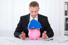 Male Architect With Piggybank Wearing Construction Helmet Royalty Free Stock Photo