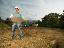 Male architect reading blueprint on worksite Royalty Free Stock Photos