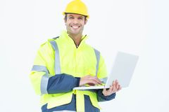 Male architect in reflective clothing using laptop Stock Images