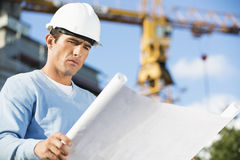 Male architect reviewing blueprint at construction site Royalty Free Stock Image