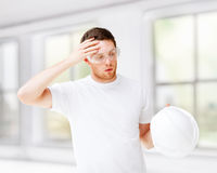 Male architect in safety glasses taking off helmet. Architecture concept - male architect in safety glasses taking off helmet Royalty Free Stock Photo