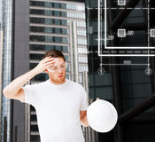 Male architect in safety glasses taking off helmet. Building, developing, consrtuction and architecture concept - male architect in safety glasses taking off Royalty Free Stock Images