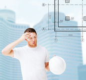 Male architect in safety glasses taking off helmet. Building, developing, consrtuction and architecture concept - male architect in safety glasses taking off Stock Images