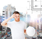 Male architect in safety glasses taking off helmet. Building, developing, construction and architecture concept - male architect in safety glasses taking off Royalty Free Stock Photo