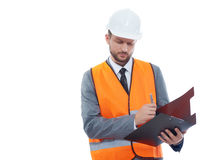 Male architect in a safety west and a hardhat writing on his cli. Building industry worker. Studio shot of a male constructionist wearing fluorescent safety vest Stock Images