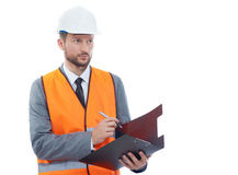 Male architect in a safety west and a hardhat writing on his cli Royalty Free Stock Images