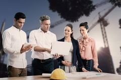 Composite image of male architect showing laptop to coworkers. Male architect showing laptop to coworkers against cranes at construction site during day Stock Image