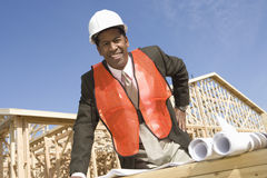 Male Architect Standing In Front Of Framework With Blueprint Stock Photo
