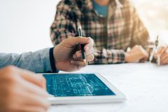 Male architect using digital tablet with architectural plan on t. Able Royalty Free Stock Photo