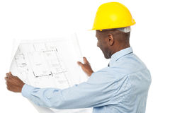 Male architect viewing blue print. Construction engineer with hardhat reviewing building plan Royalty Free Stock Photo