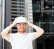 Male architect in white helmet with safety glasses. Building, developing, consrtuction and architecture concept - male architect in white helmet with safety Royalty Free Stock Photos