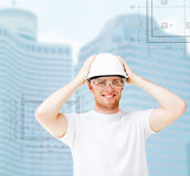 Male architect in white helmet with safety glasses. Building, developing, consrtuction and architecture concept - male architect in white helmet with safety Royalty Free Stock Image