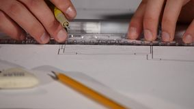 Male architect at work. Architect Hands. Ruler and a pencil in the hand of the architect. Design of the house. Engineer. Tools for drawing. Creating a drawing stock video footage