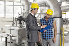 Male architect with worker discussing over clipboard in industry Royalty Free Stock Photo