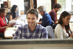 Male Architect Working At Desk With Meeting In Background Royalty Free Stock Image
