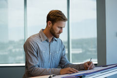 Male architect working in office. Young male architect working in office Royalty Free Stock Photo
