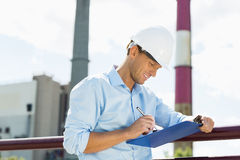 Male architect writing on clipboard at site Royalty Free Stock Photo