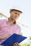 Male architect writing on clipboard at site Stock Photos