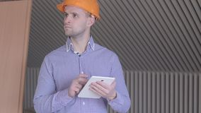 Male architector looking at the screen of his digital tablet at the building under construction. Male architector looking at the screen of his digital tablet at stock footage