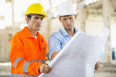 Male architects analyzing blueprint at construction site Royalty Free Stock Images