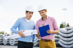 Male architects with blueprint and clipboard working at site Stock Photo
