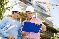Male architects with blueprint and clipboard working at site Stock Photos