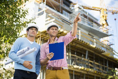 Male architects with blueprint and clipboard working at site Stock Photography