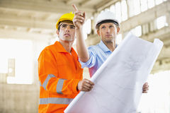 Male architects with blueprint working at construction site Stock Photos