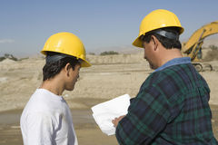 Male Architects Discussing At Construction Site Stock Photos
