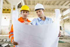 Male architects discussing over blueprint at construction site Royalty Free Stock Photo