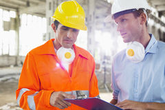 Male architects in protective workwear discussing at construction site Royalty Free Stock Photos
