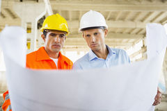 Male architects reviewing blueprint at construction site Stock Images
