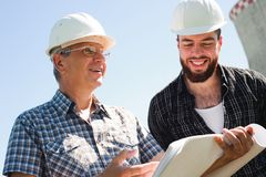 Male architects reviewing documents together at electric power plant. royalty free stock images