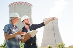 Male architects reviewing documents together at electric power plant. stock photos