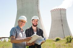 Male architects reviewing documents together at electric power plant. stock photo
