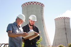 Male architects reviewing documents together at electric power plant. stock image