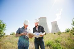 Male architects reviewing documents together at electric power plant. royalty free stock image
