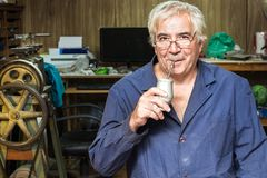 A male Argentinian craftman drinking mate. Portrait of a argentinian jeweler wearing a blue smock and drinking mate in his jewelry workshop Royalty Free Stock Photos