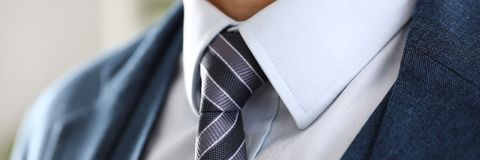 Male arm in blue suit set tie closeup Stock Images
